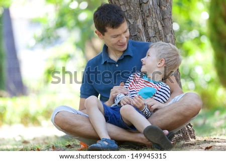 smiling happy father and his adorable son spending time together at the park