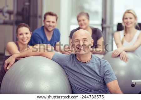 Smiling happy fit senior man in a gym class with a group of diverse people leaning on a pilates ball looking at the camera in a healthy lifestyle concept - stock photo