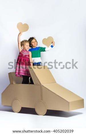 Smiling happy girl and boy near cardboard car. full length portrait - stock photo