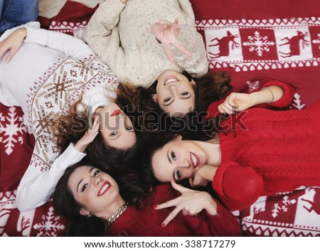 Smiling Happy girl friends group in New Year's sweater lying down on the floor close up Having fun together at winter holiday time - stock photo