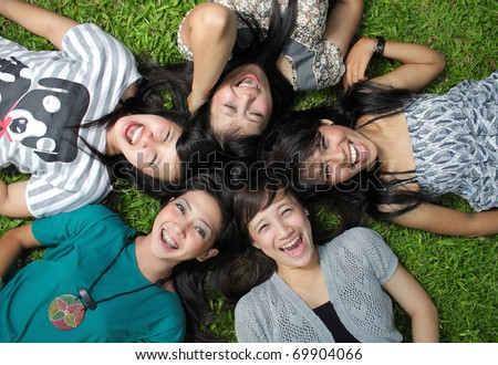 Smiling Happy girl friends group lying down in the park - stock photo