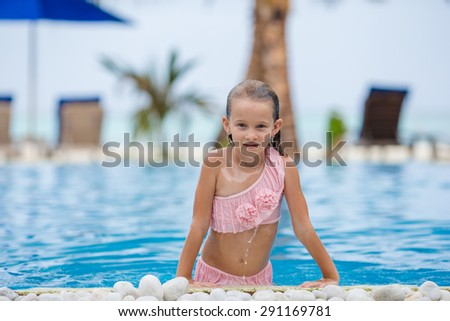 Smiling happy girl having fun in outdoor swimming pool - stock photo