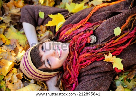 Smiling happy girl in knitted striped hat lying in autumn leaves. Close up portrait, outdoor.  - stock photo
