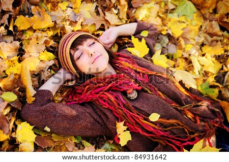 Smiling happy girl portrait, lying in autumn leaves. Outdoor. - stock photo