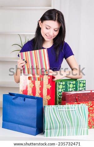 Smiling happy girl prepares bags gifts for Christmas