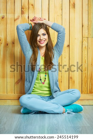 Smiling happy girl sitting on a floor. Young woman in teenager style portrait. - stock photo