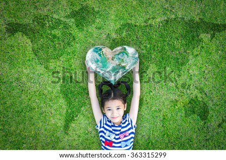 Smiling happy healthy child kid holding heart shaped green globe on world map grass background: Sustainable world concept promoting global health csr campaign: Elements of this image furnished by NASA - stock photo