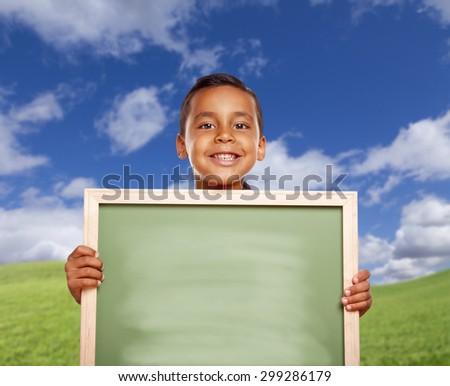 Smiling Happy Hispanic Boy In Grass Field Holding Blank Chalk Board. - stock photo