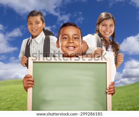 Smiling Happy Hispanic Boys and Girl In Grass Field Holding Blank Chalk Board. - stock photo