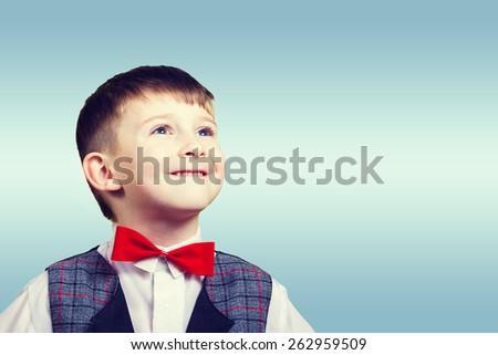 Smiling, Happy, Joyful beautiful little boy, looking up.Close-up Studio Portrait isolated on blue background. - stock photo