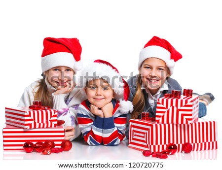 Smiling happy kids of three in Santa's hat with gift box, isolated on white - stock photo