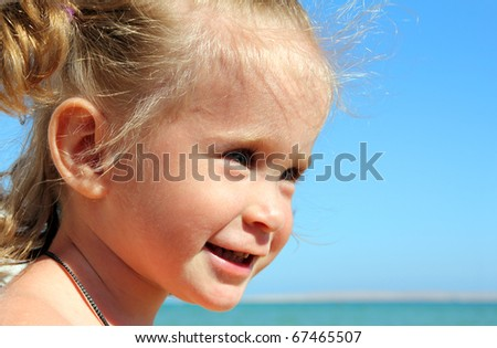 smiling happy little girl on beach near sea