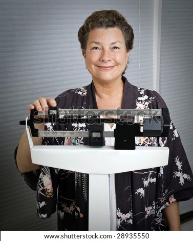 Smiling, happy, mature woman on a medical scale, pleased with the results of her weight-loss program. - stock photo