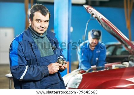 Smiling happy mechanic technician worker at car maintenance repair service station - stock photo