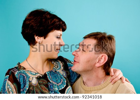 Smiling happy middle aged couple in love. Isolated on turquoise - stock photo
