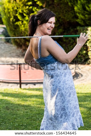 Smiling happy middle-aged woman with a golf club - stock photo