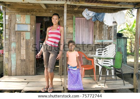 smiling happy mother daughter   porch in front of clapboard house in   Big Corn Island Nicaragua Central America - stock photo