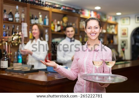Smiling happy nippy with beverages and bar crew at background - stock photo