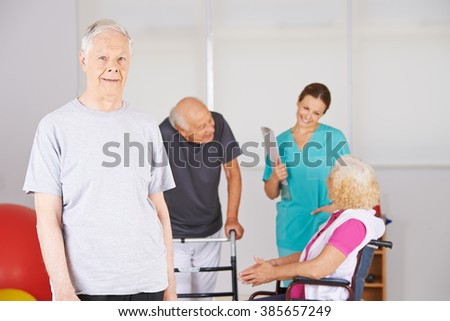 Smiling happy old man standing in front of group of senior people in a nursing home - stock photo