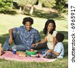 Smiling happy parents and son having picnic in park. - stock photo