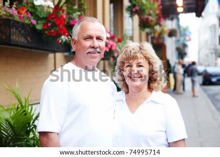 Smiling happy senior couple in the city - stock photo