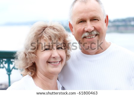Smiling happy  senior couple in the summer park - stock photo