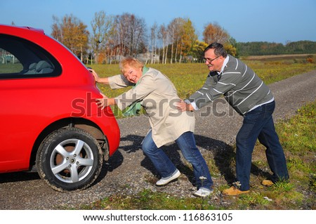 Smiling happy senior couple push the broken car - stock photo