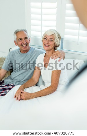 Smiling happy senior couple sitting on bed at home - stock photo