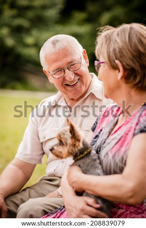 Smiling happy senior couple with their dog pet outdoor in nature - stock photo
