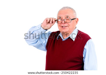 Smiling happy senior old man looking up and holds the glasses right hand. Isolated