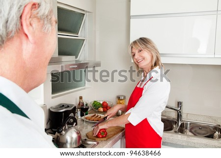 Smiling happy senior woman preparing dinner in kitchen - stock photo