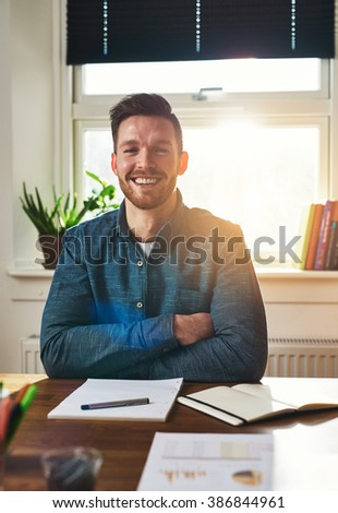 Smiling happy successful businessman sitting at his desk with folded arms laughing at the camera with paperwork on the desk in front of him