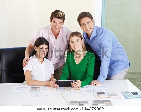 Smiling happy team of architects with tablet computer at desk - stock photo
