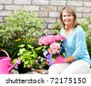 Smiling happy woman gardening near the home - stock photo