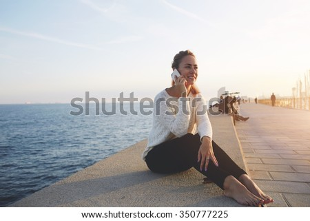 Smiling happy woman having pleasant conversation on mobile phone while sitting near sea during recreation time, young cheerful hipster girl calling with cell telephone while enjoying good day and calm - stock photo