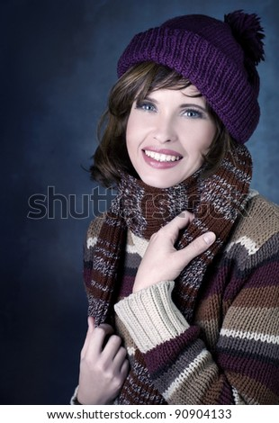 Smiling happy woman in winter clothes on dark background