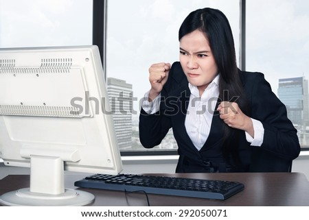 Smiling happy woman using computer with office background