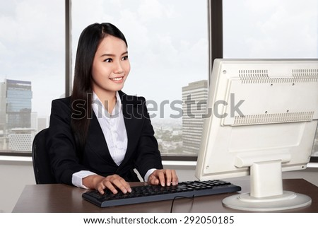 Smiling happy woman using computer with office background - stock photo