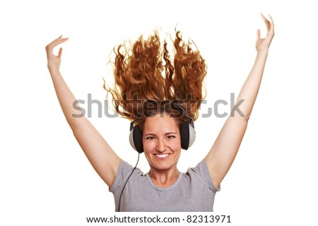 Smiling happy woman with headphones and flying hair - stock photo