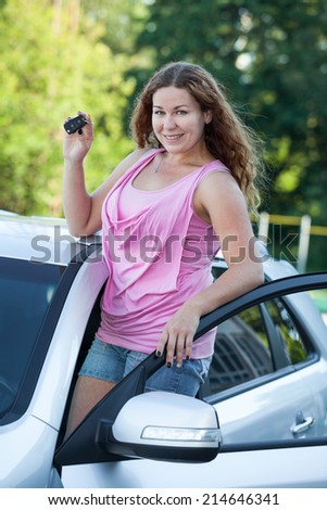 Smiling happy woman with new car and igniton key in hands - stock photo