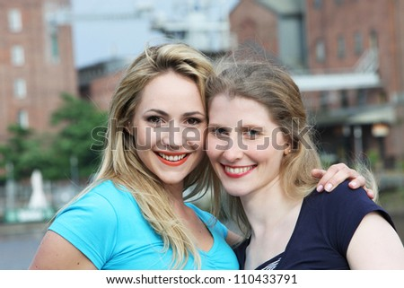 Smiling happy women in town Smiling happy women standing with their heads close together in a display of friendship in an urban environment with buildings - stock photo