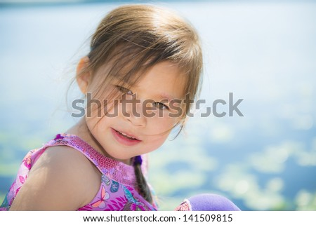 Smiling, happy 4-year old girl by a lake with waterlilies in the background