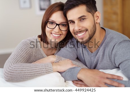 Smiling happy young couple in love posing arm in arm looking over the back of a sofa at the camera - stock photo