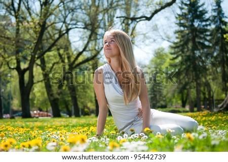 Smiling happy young terson (teen girl) sitting outdoors looking away - stock photo