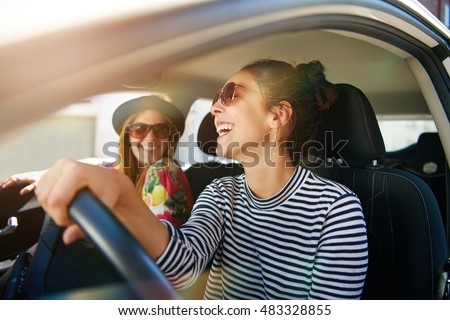 Smiling happy young woman giving her friend a lift in her car in town, profile view through the open side window with sun flare