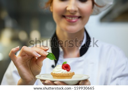 Smiling head chef putting mint leaf on little cake on plate in professional kitchen - stock photo