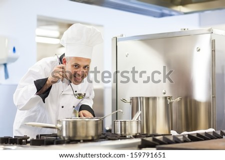 Smiling head chef tasting food from ladle in professional kitchen - stock photo