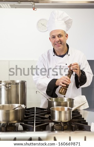 Smiling head chef using pepper mill in professional kitchen - stock photo