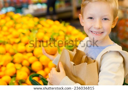 smiling healthy boy holding reusable brown bag and buying mandarin oranges at grocery store - stock photo