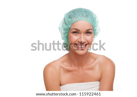 Smiling healthy woman in a shower cap isolated on white in a personal hygiene concept